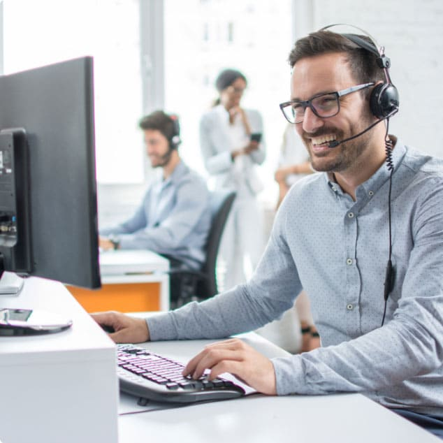 Man using a phone system for an enterprise at a desk with a headset smiling, with office staff in the distance.