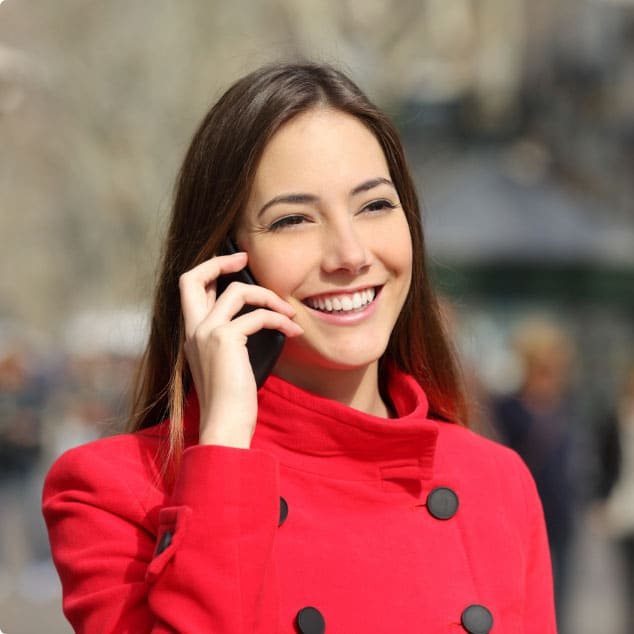 Asian woman in red jacket holding an enterprise phone to her ear