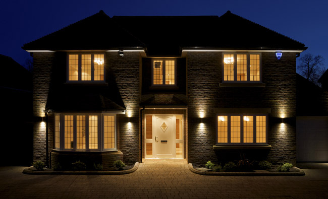Residential home with outdoor security flood lights on at night.