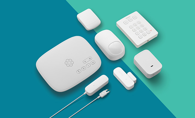 Ooma complete home security system with camera, sensors and all parts against a blue and green background.