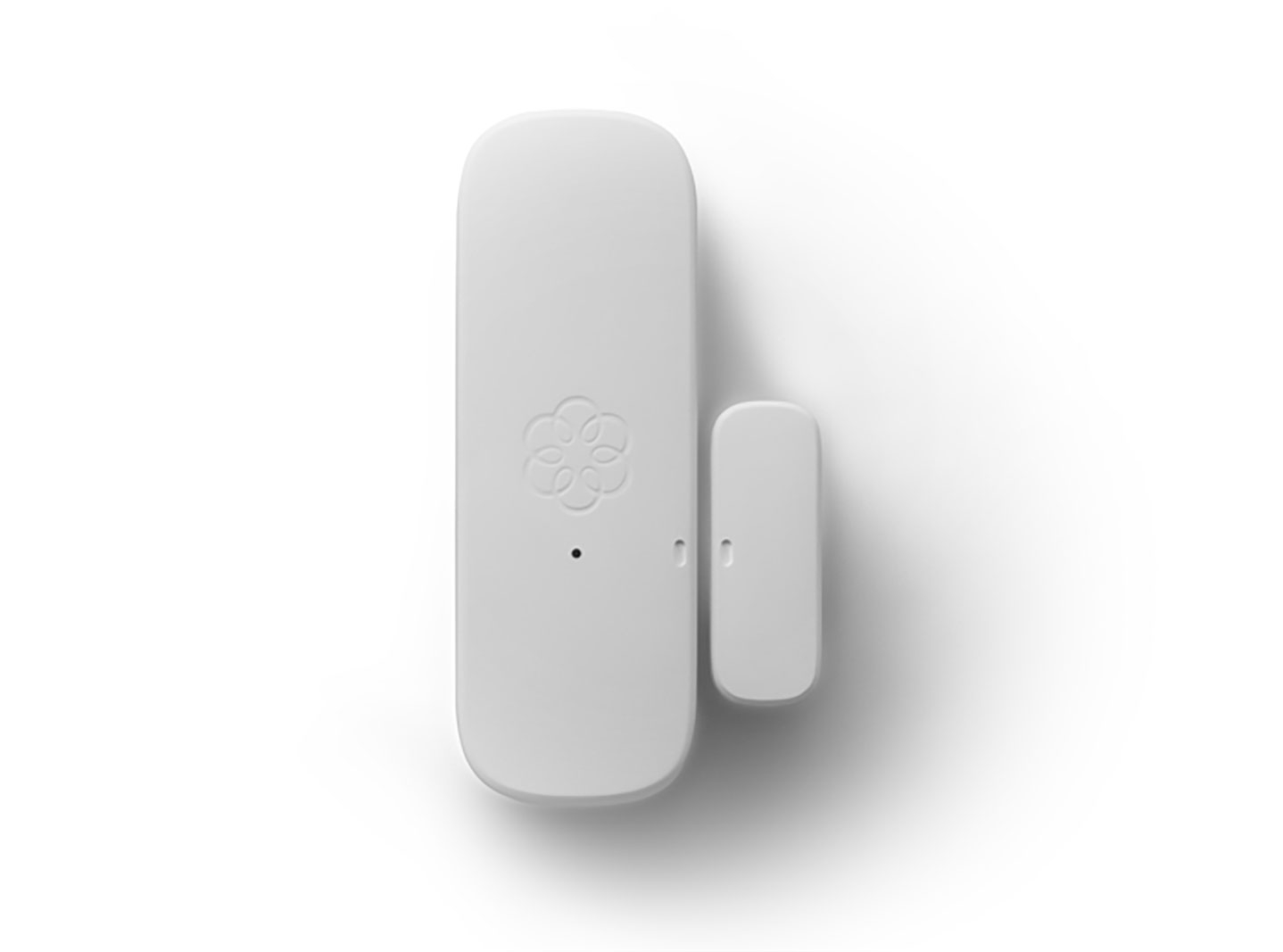 Door and window sensor used in home security with black and white backdrop.